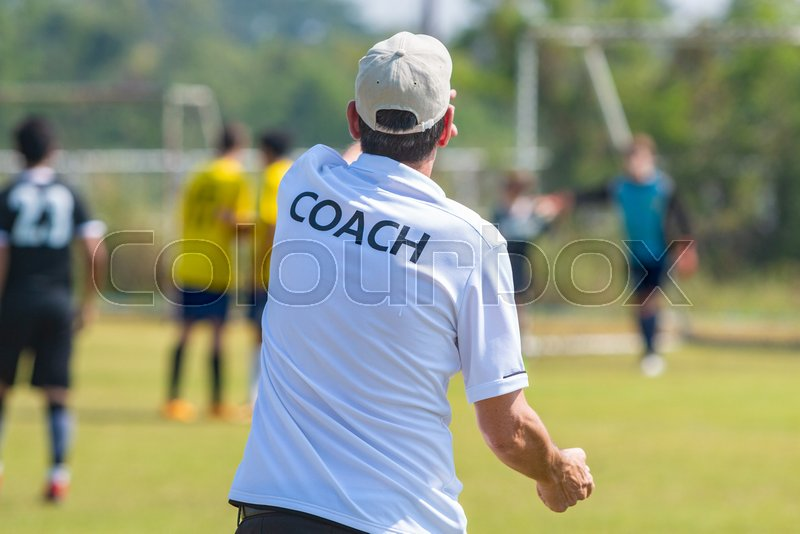 Back view of male football coach in white COACH shirt at an outdoor football field giving direction to his football team, stock photo