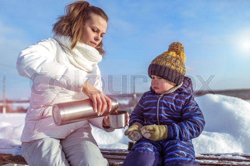 Young mother pours a mug of tea from a thermos. Little boy child looks at the mug. In winter, in the city on a bench in a snowy courtyard. Woman caring for her son, stock photo
