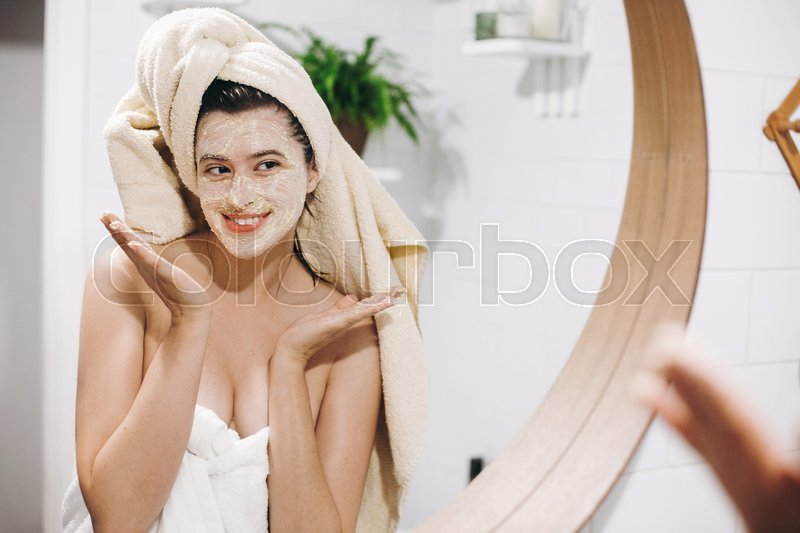 Young happy woman in towel applying organic face scrub and looking at round mirror in stylish bathroom. Girl making facial massage, peeling and cleaning skin on ..., stock photo