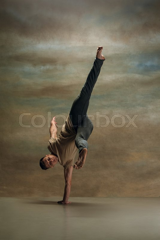 The young man dancing in contemporary stile of ballet at studio on gray background, stock photo