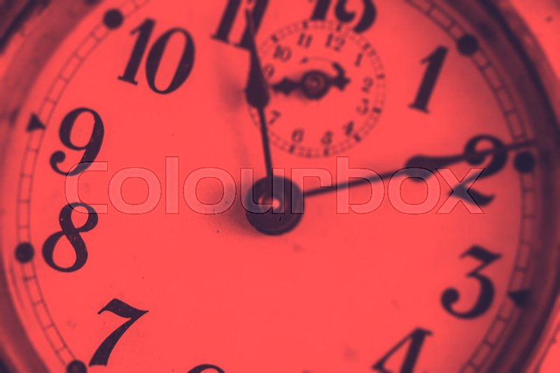 Detail of the hands of an ancient analogue clock with a duotone effect, stock photo