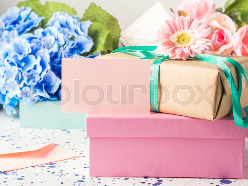 Blank pink card and stacked gift boxes. Flowers. Woman, mother, Valentine day greeting card. Copy space, stock photo