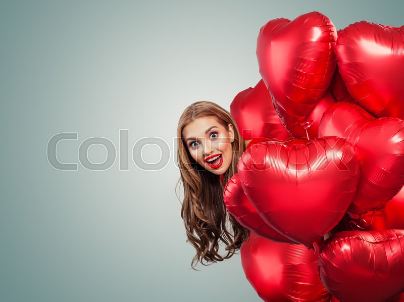 Happy surprised woman withred balloons. Perfect smiling girl with red lips makeup portrait. Surprise, valentines people and Valentine\'s day banner background with ..., stock photo