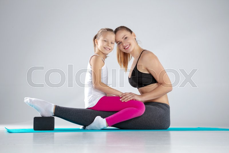 Beautiful young smiling caucasian woman and sportive girl sitting on her legs and looking in camera on blue mat with yoga block, stock photo