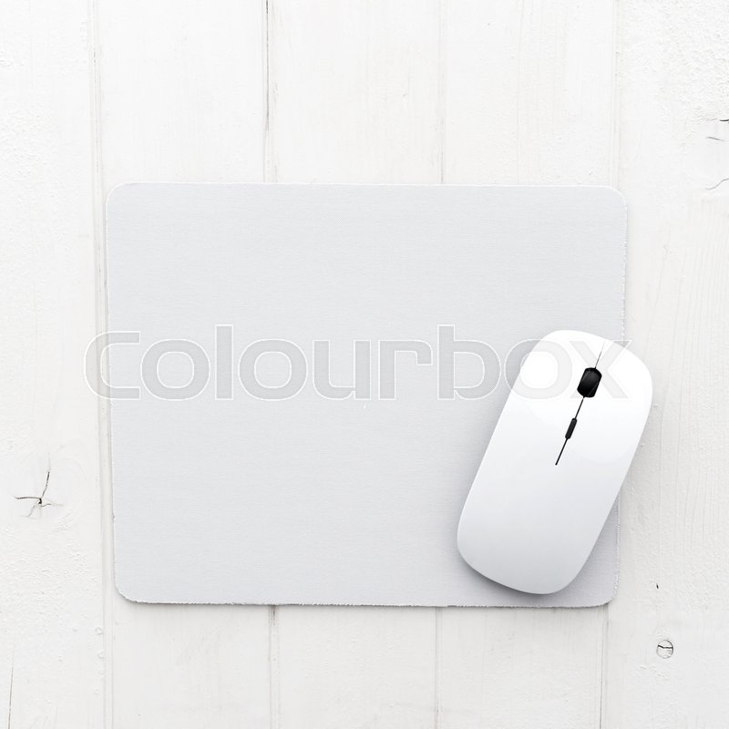 White wireless mouse on a mouse pad, top view, stock photo