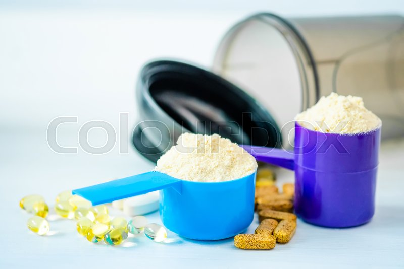 Sport Pills, vitamins and protein powder with brown bottle composed on a table, stock photo