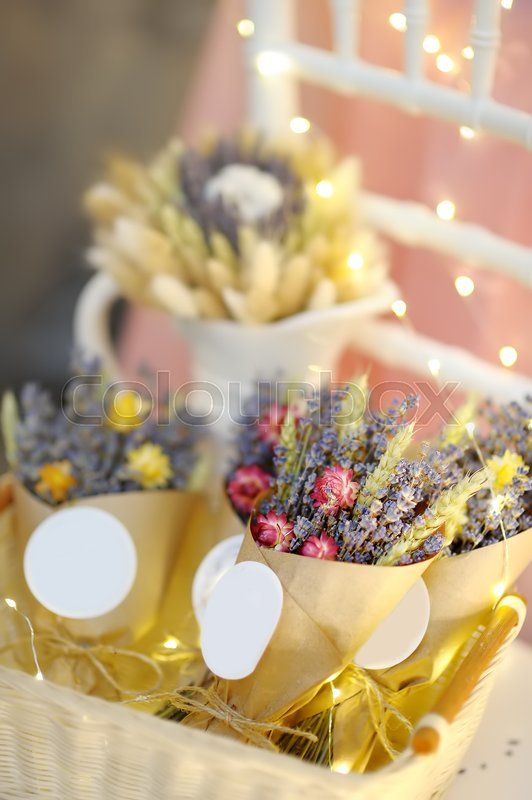 Beautiful dried flowers in paper boxes with lights on background. Wedding decorations close up. Floral design, stock photo