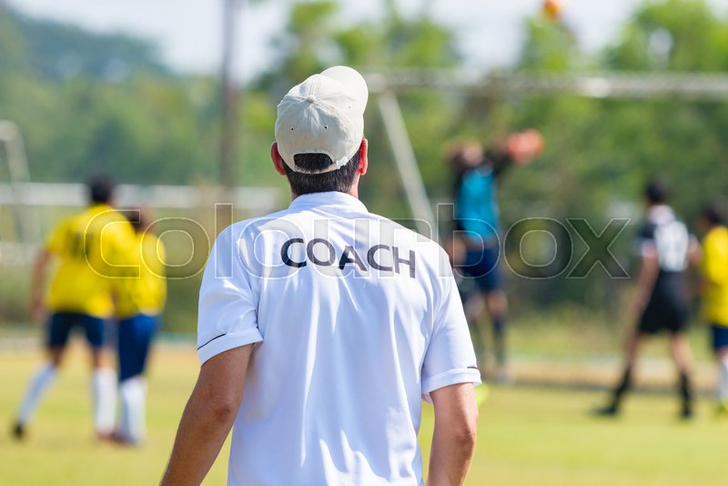 Back of football coach wearing white COACH shirt at an outdoor sport field coaching his team during a game, good for sport or coaching concept, stock photo
