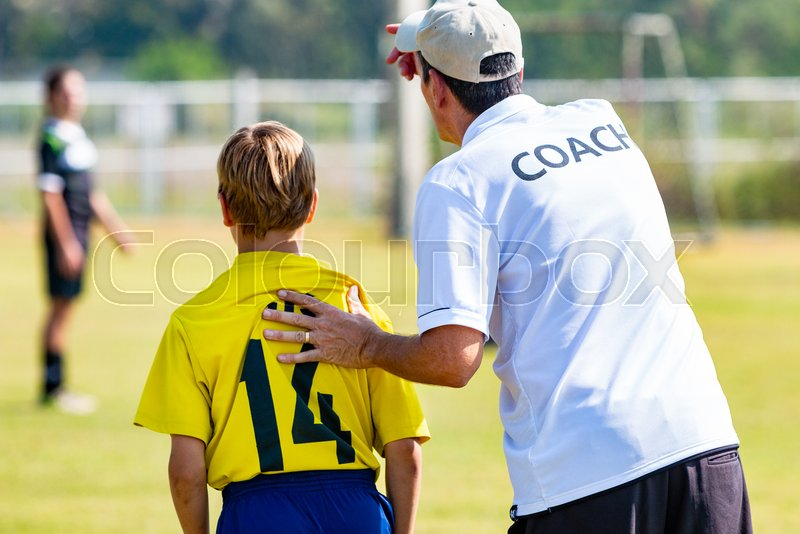 Back view of male football coach in white COACH shirt at an outdoor sport field sending his young boy player in the game, good for coaching or football concept, stock photo