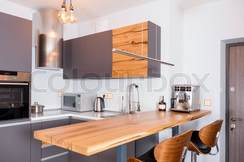 Modern kitchen interior with lights on. Brown wooden table and bar stools, coffee machine. Contemporary interior with loft elements, stock photo