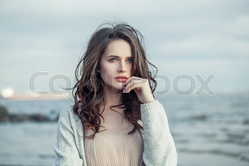 Lovely girl outdoors portrait. Cute female model face on blue water background, stock photo