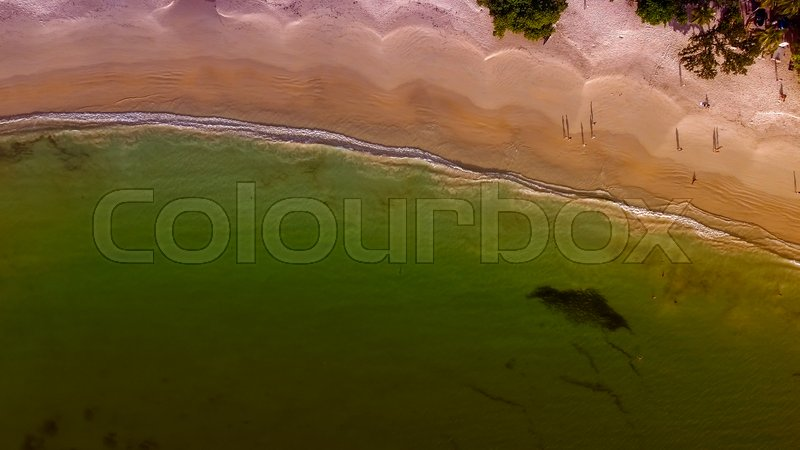Beautiful aerial overhead view of ocean beach with crystal clear water, stock photo