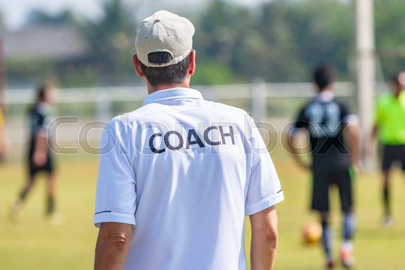 Back of male football coach wearing white COACH shirt at an outdoor sport field coaching his team during a game, good for sport or coaching concept, stock photo
