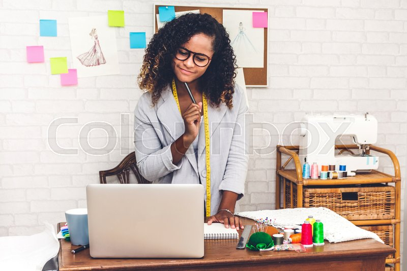 Smiling african american black woman fashion designer working with laptop computer at workshop studio, stock photo