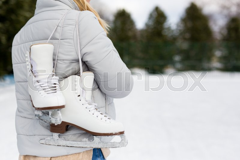 Back view of woman holding ice skates at rink in winter park, stock photo