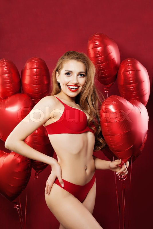 Excited woman with balloons red heart. Sexy model girl in red sensual underwear. Valentine\'s day concept . Positive emotion. Expressive facial expressions, stock photo