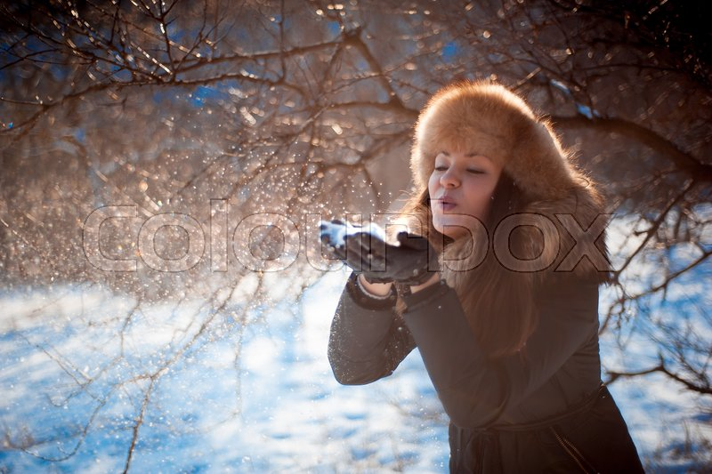 Girl in hat with ear flaps blowing on the snow, stock photo