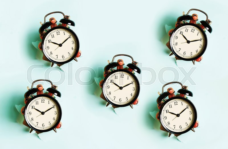 Chaotic pattern of hand holding black alarm clock through hole in blue paper background. Wake up alert concept. Morning routine. Banner with copy space, stock photo