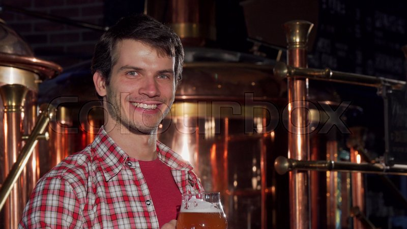 Professional male brewer drinking craft beer at his own brewery. Handsome young happy brewery worker smiling to the camera, sipping delicious beer. Small business ..., stock photo