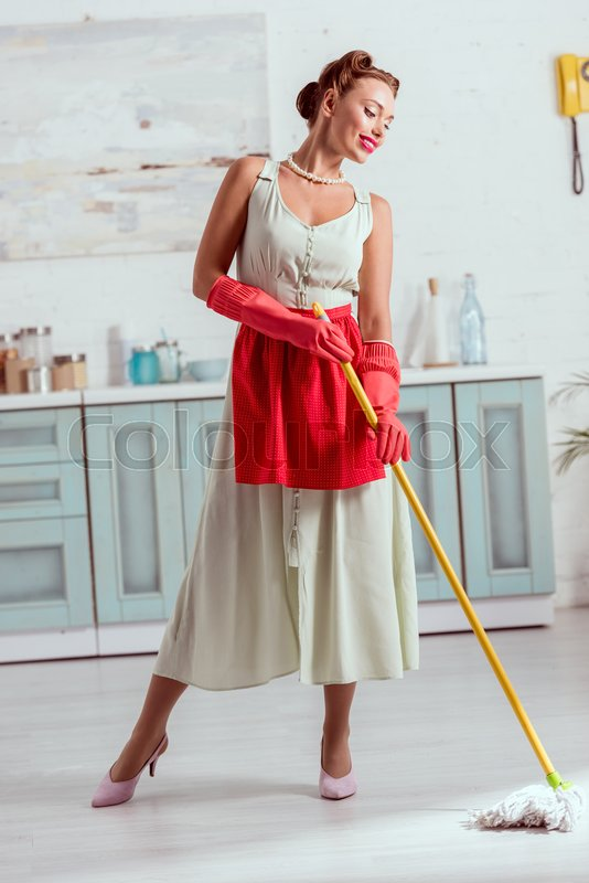 Smiling pin up cleaning kitchen floor with yellow mop, stock photo