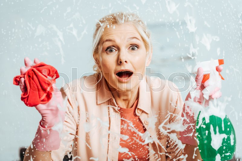 Shocked senior woman in rubber gloves cleaning window, stock photo