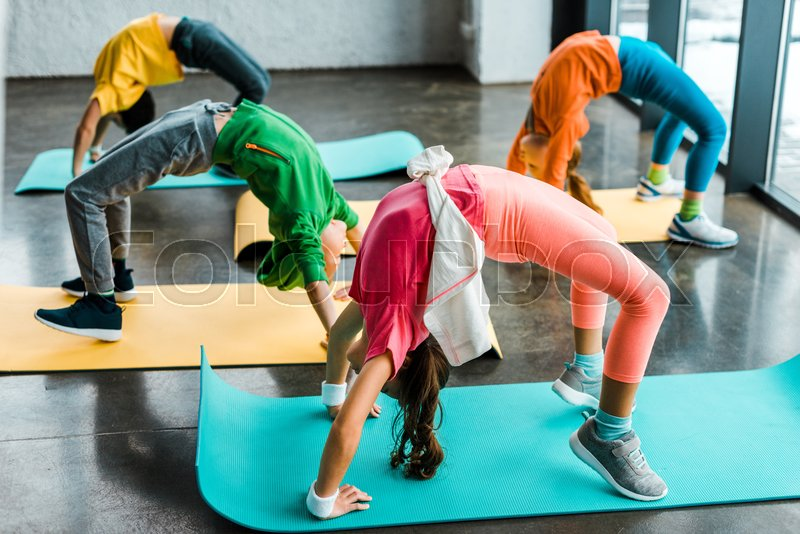 Kids doing gymnastic exercise on fitness mats, stock photo