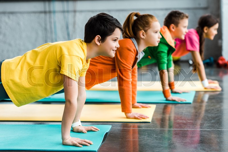 Preteen kids doing plank exercise in gym, stock photo