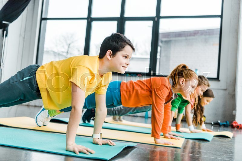 Preteen kids doing plank exercise together in gym, stock photo