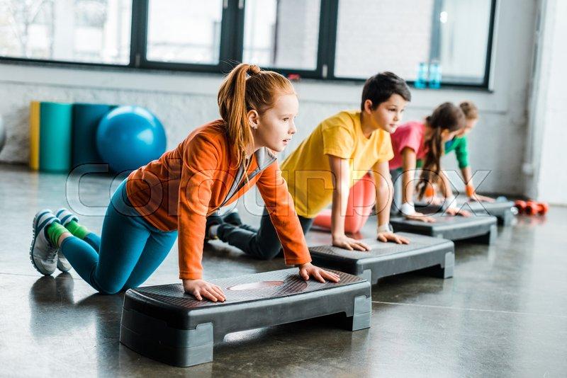 Kids using step platforms while doing push-up exercise, stock photo