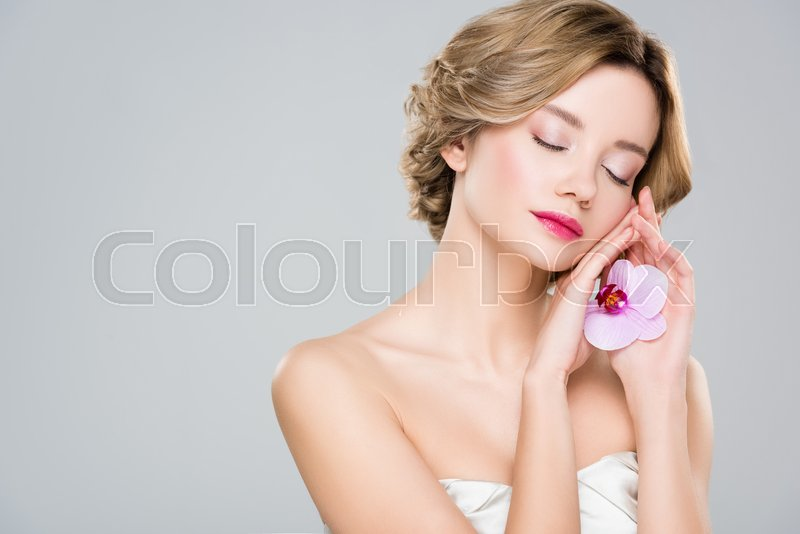 Young tender woman with closed eyes holding purple orchid isolated on grey, stock photo