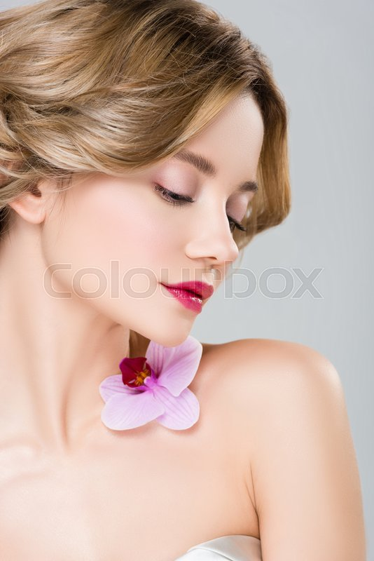 Young tender woman with purple orchid on shoulder isolated on grey, stock photo