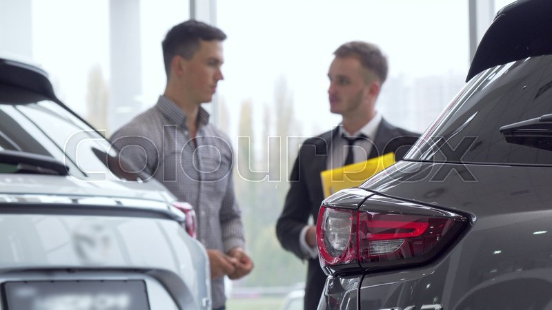 Selective focus on a car, male customer talking to auto dealer on the background. Man buying new automobile, getting an advice from salesman. Ownership, insurance ..., stock photo