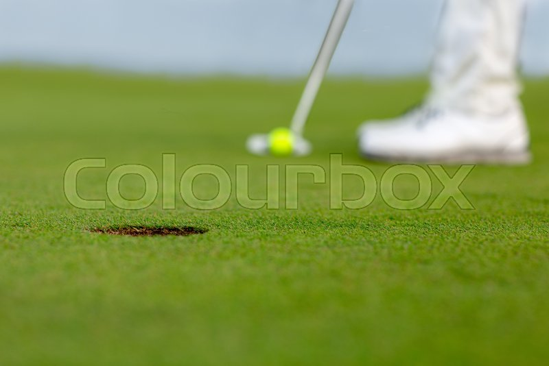 Image of golf hole on green. Golfer is ready to putt a yellow ball into hole, stock photo