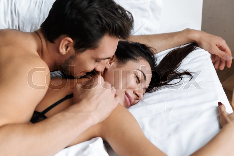 Photo of half-naked couple man and woman hugging together, while lying in bed at home or hotel apartment, stock photo