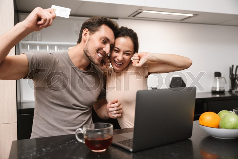 Photo of ecstatic couple man and woman using laptop with credit card, while sitting in kitchen, stock photo