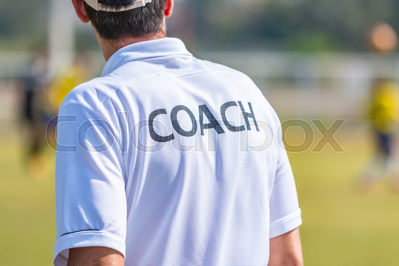 Back view of male sport coach in COACH shirt at an outdoor sport field, good for sport or coaching concept, stock photo