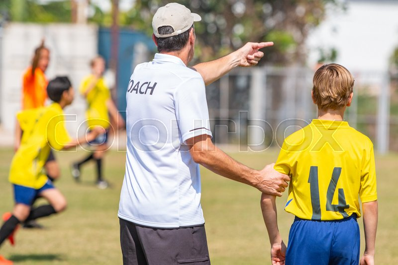Back of male football coach wearing white COACH shirt at an outdoor sport field about to send in his young boy player in the game, good for coaching or sport concept, stock photo