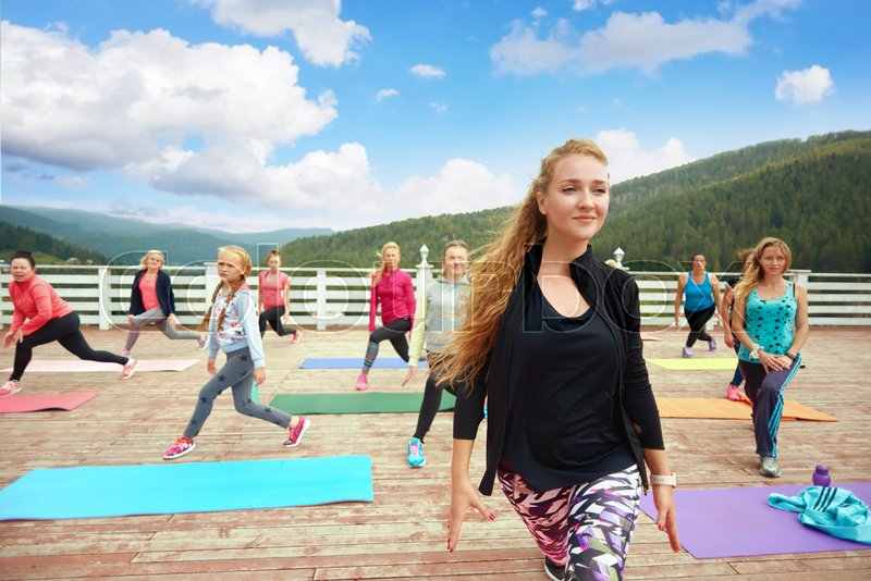 Professional coach training fitness, showing moves. Beautiful woman coaching fitness group on fresh air. Girls and women wearing in sportswear doing twisting ..., stock photo