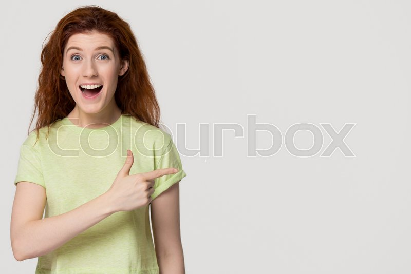 Excited thrilled redhead woman pointing finger at copy space surprised by unbelievable sale, amazed happy red-haired girl indicating advertising cheap offer isolated ..., stock photo