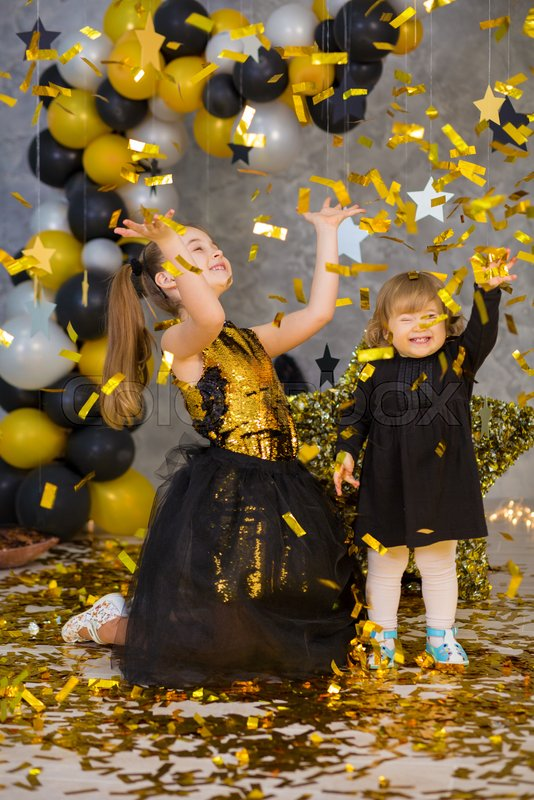 Movie super star girls models posing in studio shoot with golden star and colorful baloons wearing stylish gold airy dress with shining bow tie.Super star pillow ..., stock photo