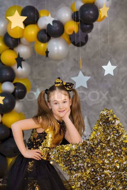 Movie super star girl model posing in studio shoot with golden star and colorful baloons wearing stylish gold airy dress with shining bow tie.Super star pillow ..., stock photo