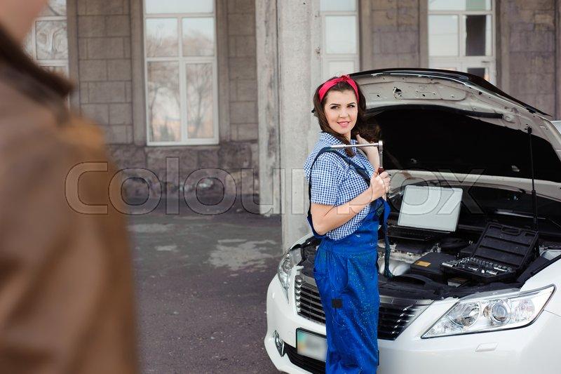 Professional auto woman mechanic and man repair auto outdoors, stock photo
