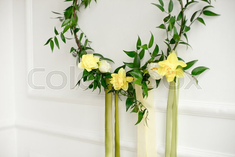 Close-up green wreath of narcissus and plants on the white wall, stock photo