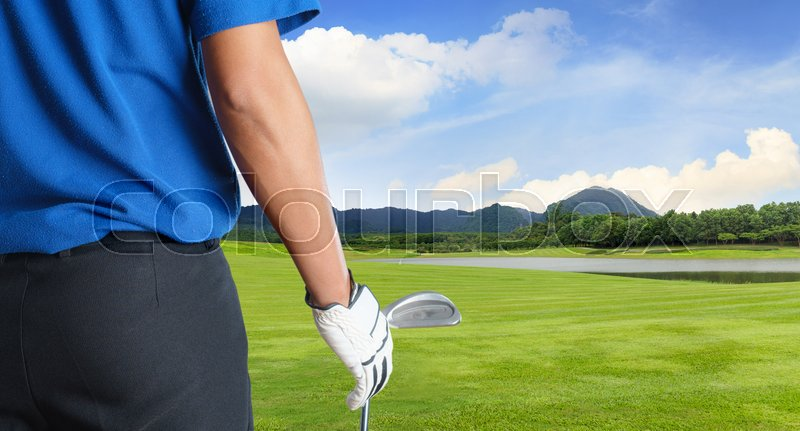 Golf player holding a golf club in golf course, stock photo