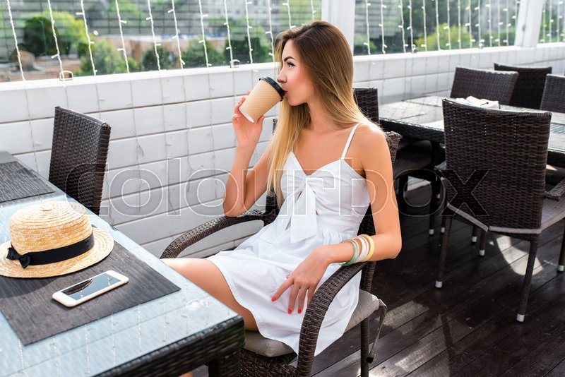 Beautiful girl in summer cafe. In hands of cup of coffee or tea, breakfast and lunch in a white dress. On the table is a smartphone and a straw hat. Rest after a ..., stock photo