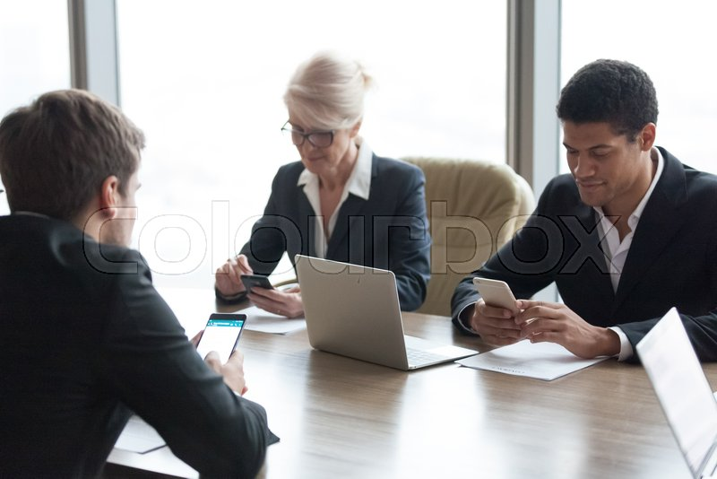 Diverse business people executives holding phones using smartphones apps at office meeting working on cellphones online, corporate employees businessmen and ..., stock photo
