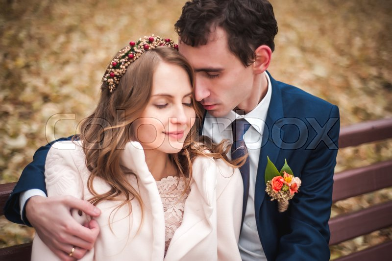 The beautiful bride and handsome groom sitting on a bench in the autumn park, stock photo