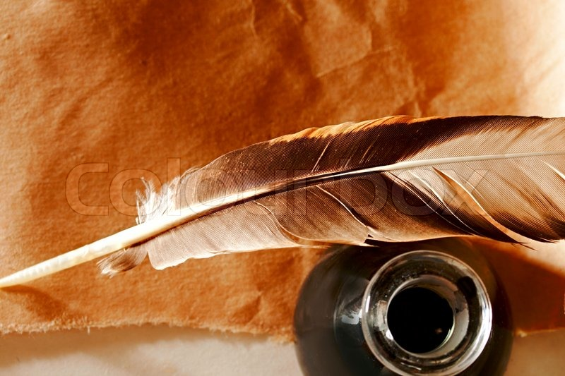 Feather And Ink Bottle On Paper Background Stock Photo