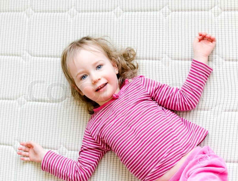 cute little girl lying on a mattress stock photo colourbox. Black Bedroom Furniture Sets. Home Design Ideas