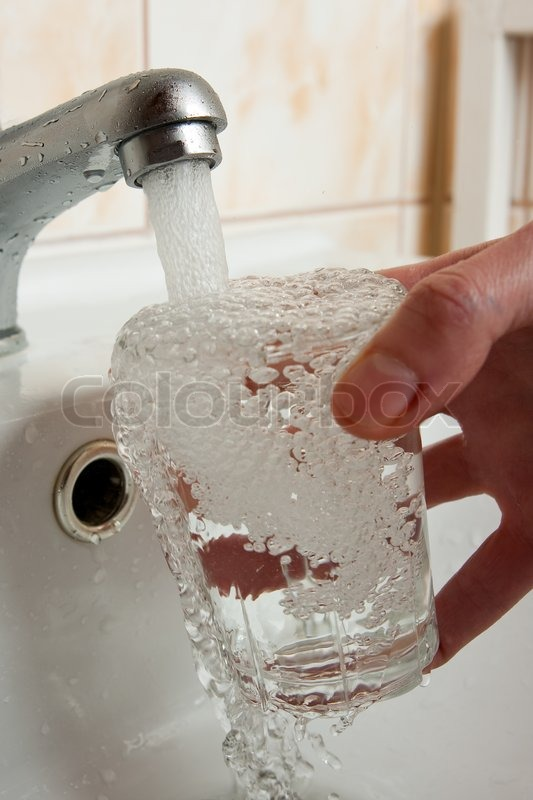 Filling glass of water, stock photo